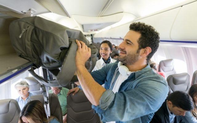 機内で荷物をしまう乗客